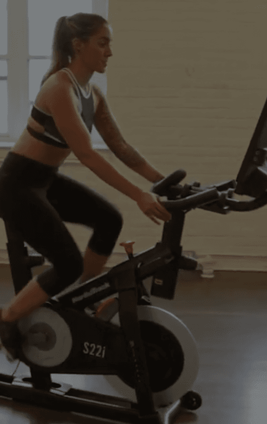 A woman riding an exercise bike.